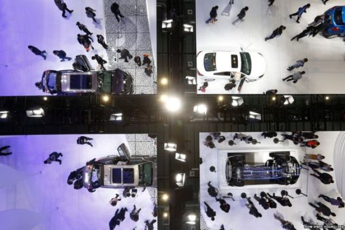 Visitors and cars are seen reflected on ceiling mirrors at the Buick booth at the Shanghai International Automobile Industry Exhibition