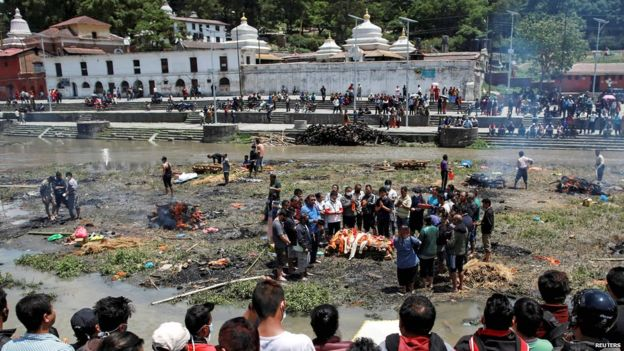 People pray before cremating the body of a victim of Saturdays earthquake, alongside a river in Kathmandu, Nepal (27 April 2015)