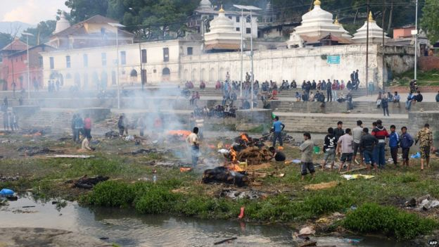 People burn the bodies of earthquake victims at a mass cremation at Pashupatinath in Kathmandu on April 26, 2015.