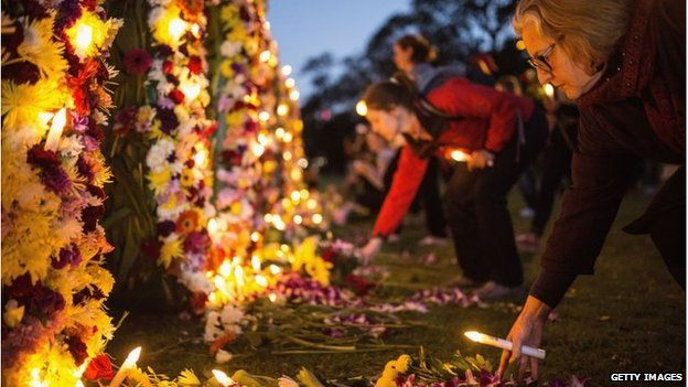 A woman puts flowers on a tribute wall in Sydney for Andrew Chan and Myuran Sukumaran