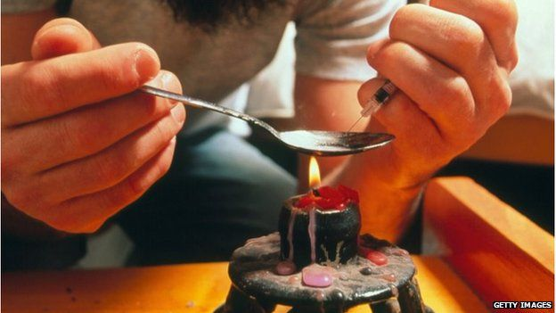 A man heats heroin in a spoon over a flame