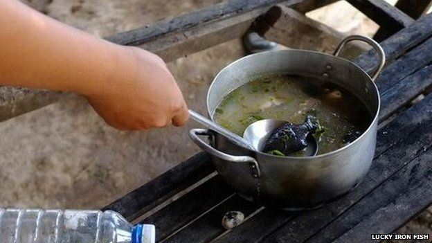 An iron fish being stirred into soup in Cambodia