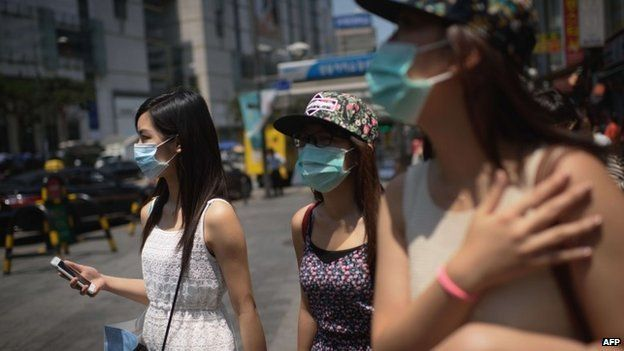 Tourists wearing face masks walk in the popular Myeongdong shopping area in Seoul on June 4, 2015.