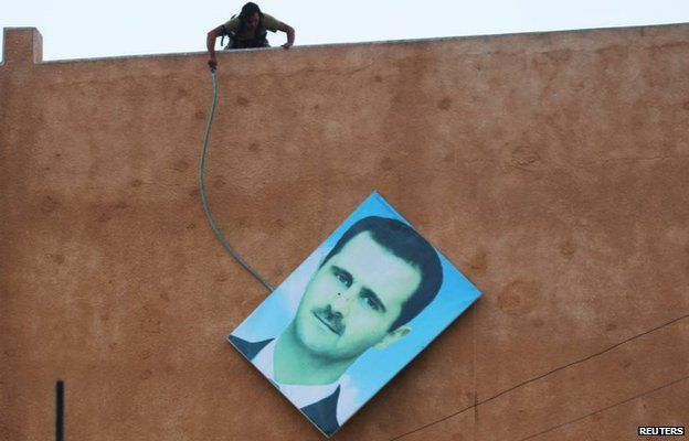 A rebel fighters removes a portrait of Syrian President Bashar al-Assad in the northern town of Ariha (29 May 2015)