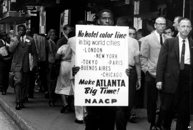 "Man protesting and holding a sign reading: ""No hotel color line"""