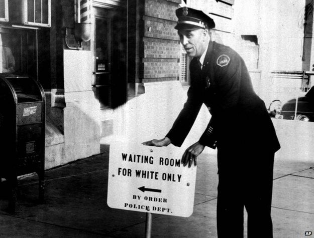 """Policeman with a sign reading: """"Waiting room for white only by order police dept."""""""