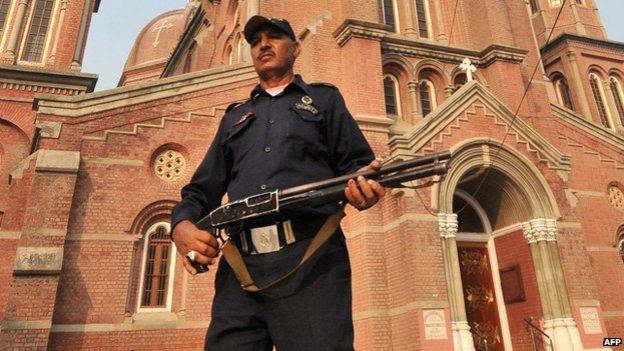 Guard outside Lahore church, 2013