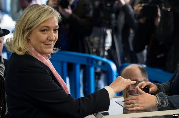 Marine Le Pen smiles as she casts her ballot during the first round of the French departmental elections on 22 March 2015 in Henin-Beaumont