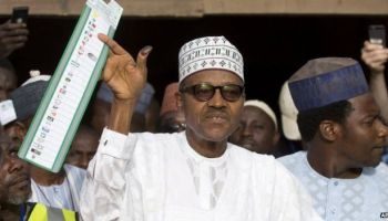 Opposition candidate Gen Muhammadu Buhari holds his ballot paper in the air before casting his vote in his home town of Daura, northern Nigeria 28 March 2015