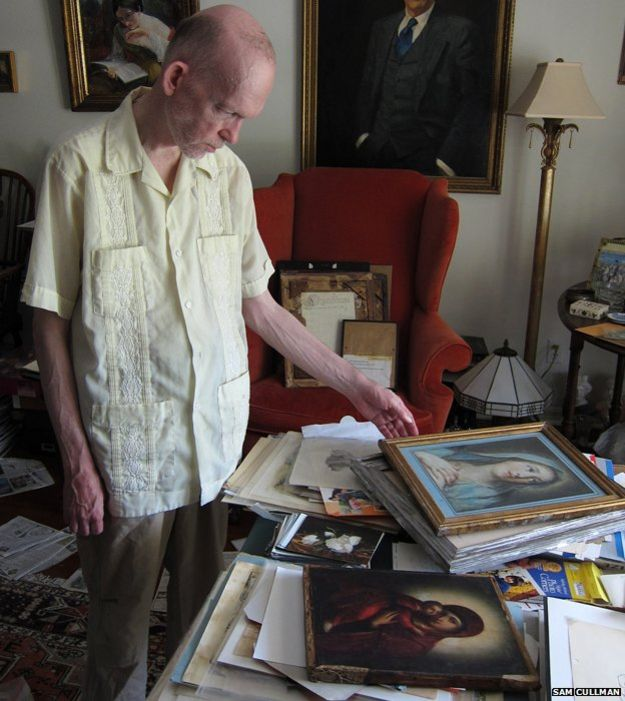 Mark Landis at home with some of his pictures