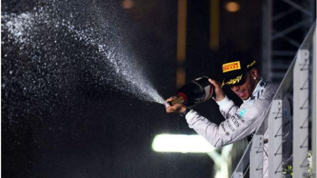 Hamilton menyemprotkan sampanye kemenangan kepada pendukung