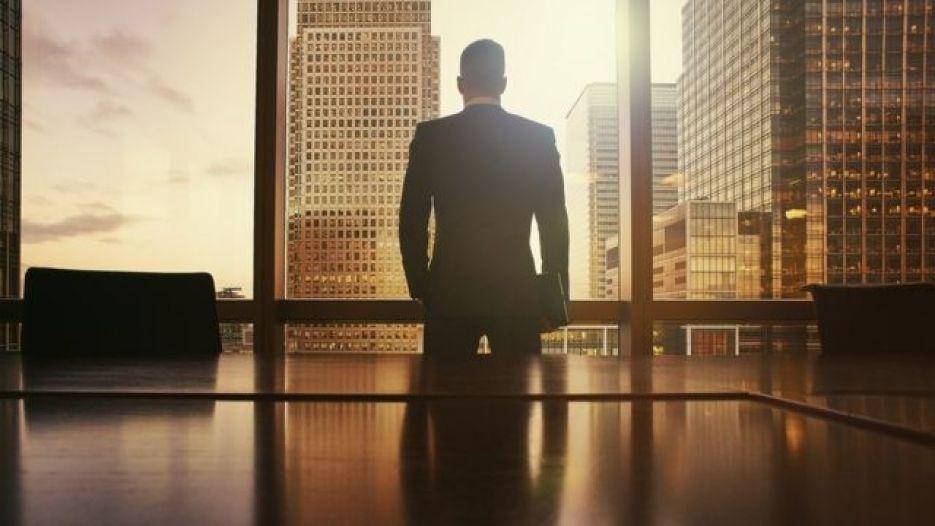homem de terno observa vista de escritório