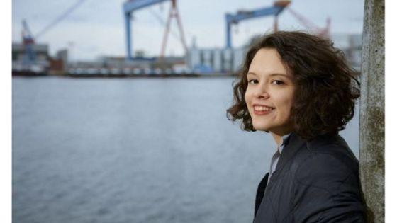 Foto de Delara Burkhardt sorrindo, de perfil, encostada em uma parede em frente ao rio urbano