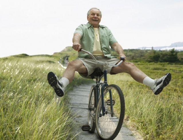 Homem com cabelos brancos anda de bicicleta animado