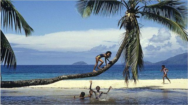 Praia em Seychelles com crianças brincando