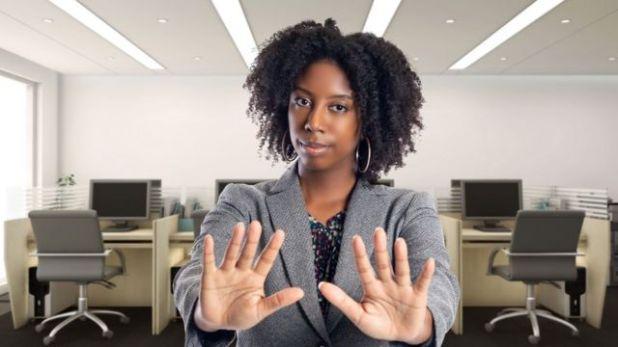 سيدة تقف في مكتب وتشير بيدها بالرفض
