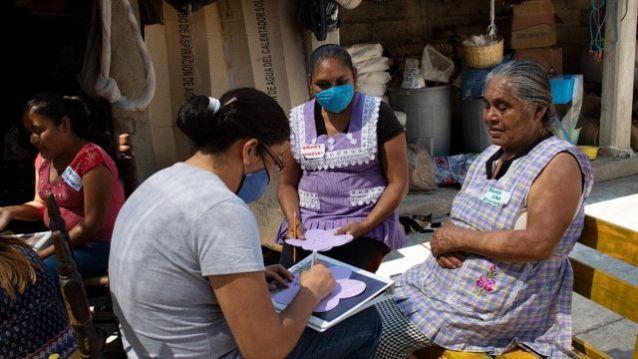 Integrante de Pure Earth falando com trabalhadoras de cerâmica