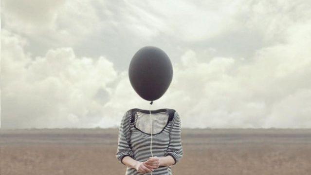 Uma pessoa segurando um balão no lugar da cabeça