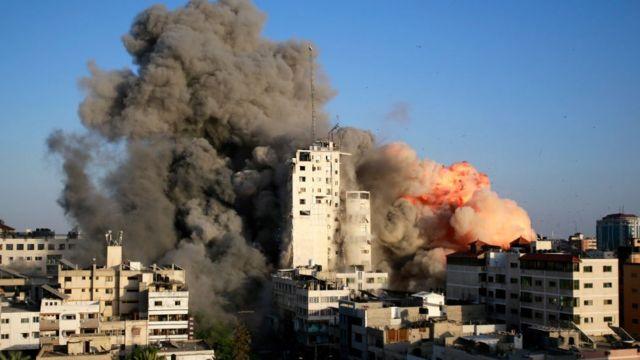 Fumaça e chamas sobem de uma torre destruída por ataques aéreos israelenses em Gaza.