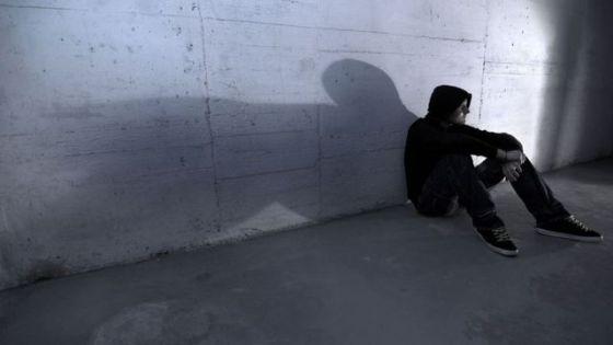 Adolescente sentado na parede