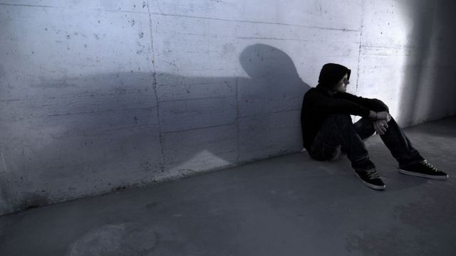 Teenager sitting on wall