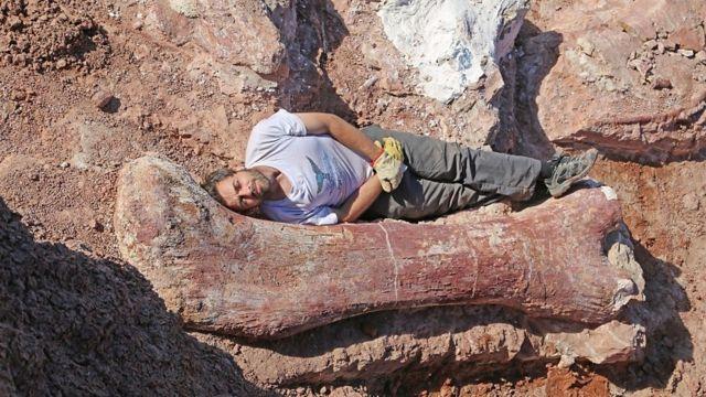 Diego Pol deitado ao lado de um osso de dinossauro
