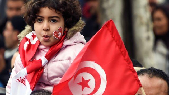 طفلة تحمل علم تونس