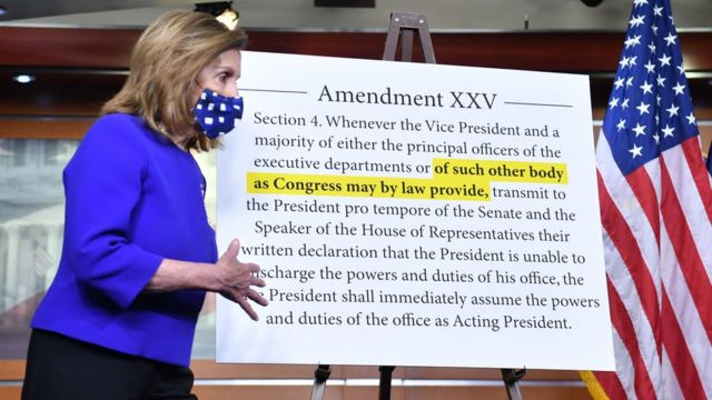 A woman in front of the text of the 25th Amendment