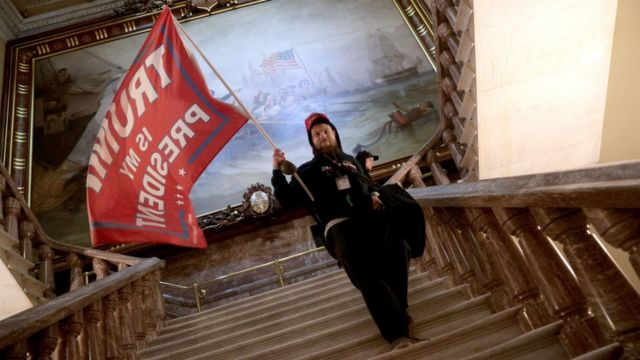 Un simpatizante de Donald Trump sostiene una bandera en apoyo al presidente mientras baja por las escaleras de una sección del Capitolio de Estados Unidos tras haber tomado el edificio.