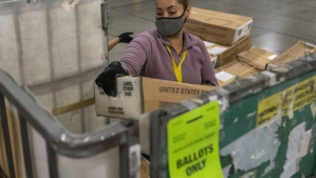 عاملة في البريد تفرغ آلاف الصناديق المليئة بالأصوات في ولاية أوريغون