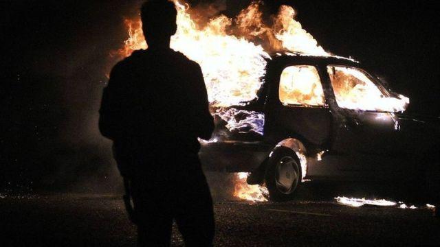 Carro pegando fogo durante protesto