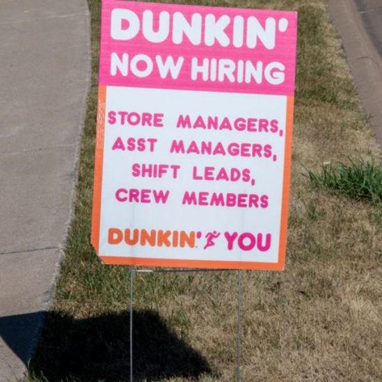Cartel de Dunkin Donuts ofreciendo empleo.