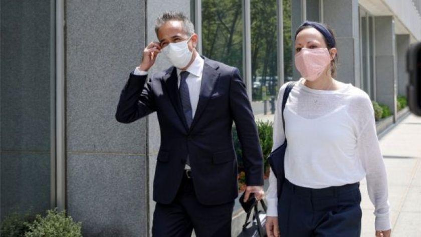 Woman walks beside a man in a suit outside a building, both wearing masks.