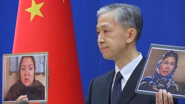 2021年2月23日,外交部发言人王文斌在中国北京举行的新闻发布会上讲话时手持照片。