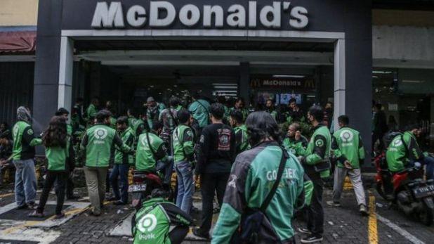 بعض عُمال شركات توصيل الطلبات ينتظرون أمام أحد فروع ماكدونالدز