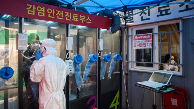 A man talks to a nurse during a coronavirus test at a test booth outside Yanghee Hospital in Seoul in March. 2020