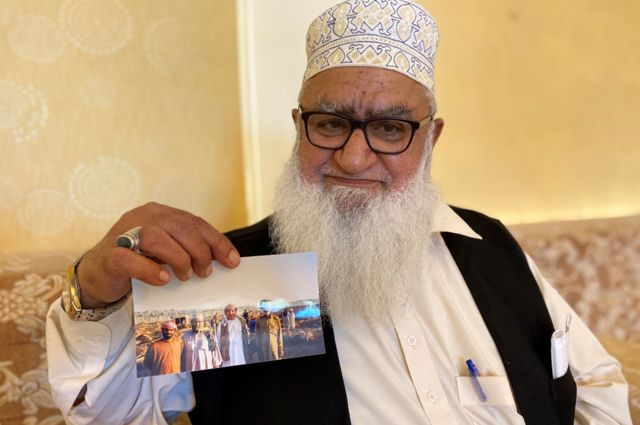 Haji Hanif displays a photo of a fishing party from the 1980s