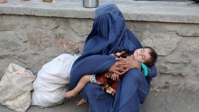 Una mujer afgana con su hijo en brazos