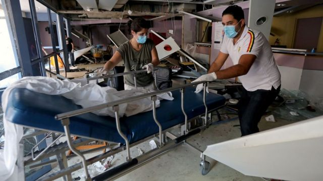 Staff move a gurney in a damaged hospital
