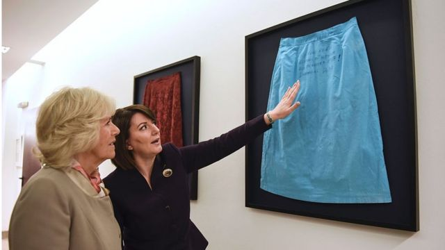 Former Kosovar president, Atefeh Yahya Agha, takes Camila, Duchess of Cornwall, on an exhibit showing the skirts of war rape survivors. Photo taken in March 2016