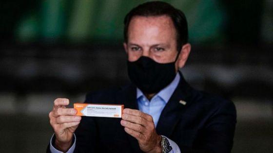 Foto de João Dória, governador de São Paulo, segurando embalagem CoronaVac