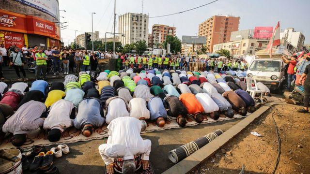 Lübnan'ın Trablus kentinde, 2019'daki hükümet protestoları sırasında toplu namaz kılan Hizb-ut Tahrir üyeleri.