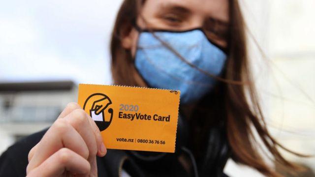 वोटर कार्ड दिखाती एक महिला मतदाता