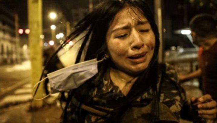 Em foto noturna, mulher chora em meio a manifestação na rua
