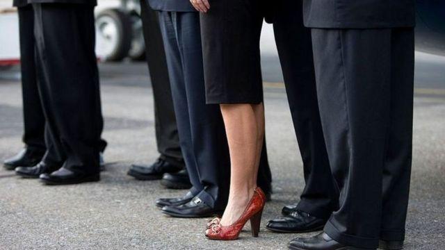 رجال بالملابس الرسمية تتوسطهم سيدة