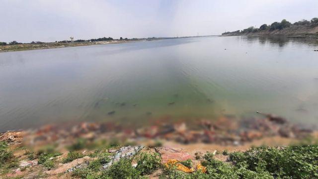 Image floue de corps flottant dans le Gange et s'empilant sur la rive du fleuve.