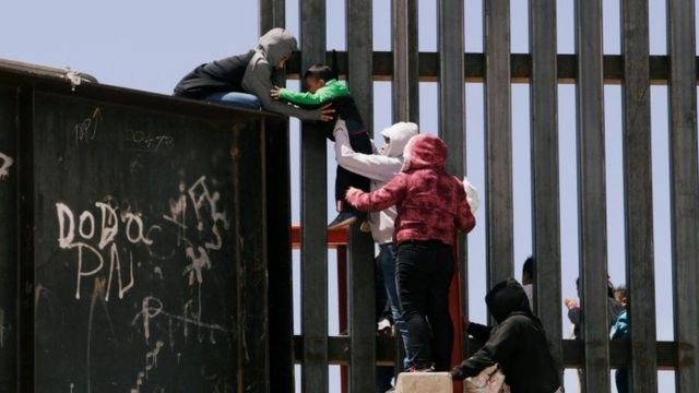 A young child passes over a border wall in the United States