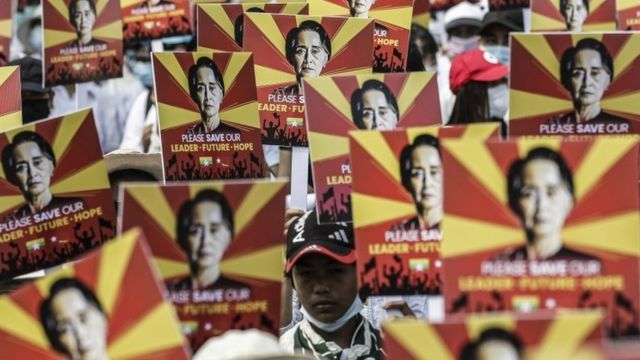 Myanmar protesters hold up images of jailed leader Aung San Suu Kyi