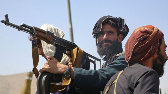 Three Taliban fighters, one of them armed and looking towards the camera