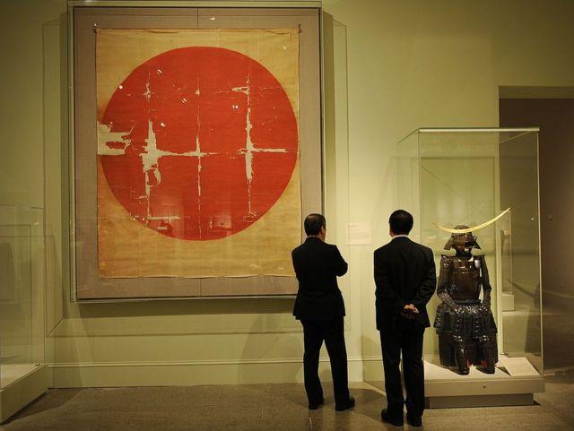 """Bandera histórica japonesa del siglo XVI al lado de una armadura samurai en la exhibición """"El arte del samurái: armas y armaduras japonesas, 1156-1868"""" en 2009 en el Metropolitan Museum of Art de Nueva York."""
